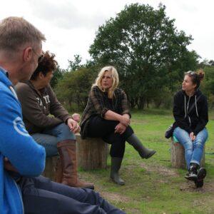 4 personen zitten met elkaar in gesprek op boomstammen midden in het duingebied van het Nationaal Park Zuid Kennemerland, zij zijn buiten aan het vergaderen en zitten er ontspannen bij