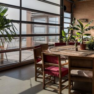 ronde houten vergadertafel met stoelen met suede zichtbaar met uitzicht door de ramen van de zee
