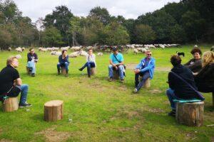 groep zit buiten op boomstammen naar elkaar te luisteren, ze zitten op een open plek met gras met bomen eromheen in duingebied met op de achtergrond kudde schapen