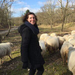 karin, eigenaar van buitendag, staat tussen de schapen in het duingebied, het is midden in de winter, de zon schijnt en een blauwe lucht is zichtbaar achter de bomen