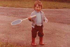oude foto van eigenaar van 2 jaar oud op rode laarsjes met badminton racket die buiten speelt